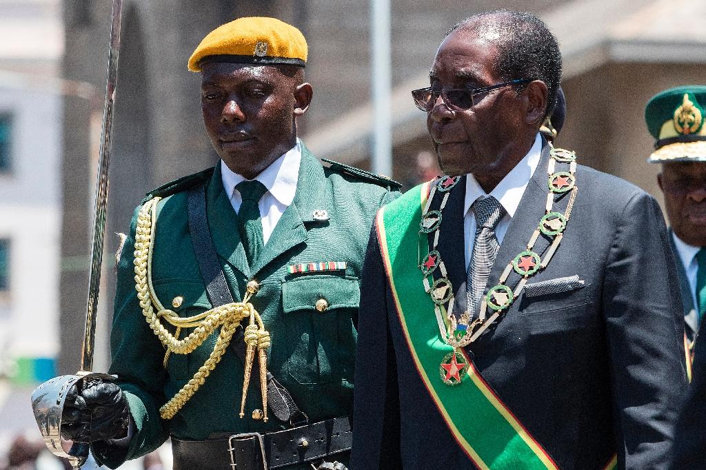 Zimbabwe's President Robert Mugabe (R) inspects an honor guard during the official opening of the fourth session of the eight Parliament of Zimbabwe on October 6, 2016 in Harare (AFP Photo/Jekesai Njikizana)