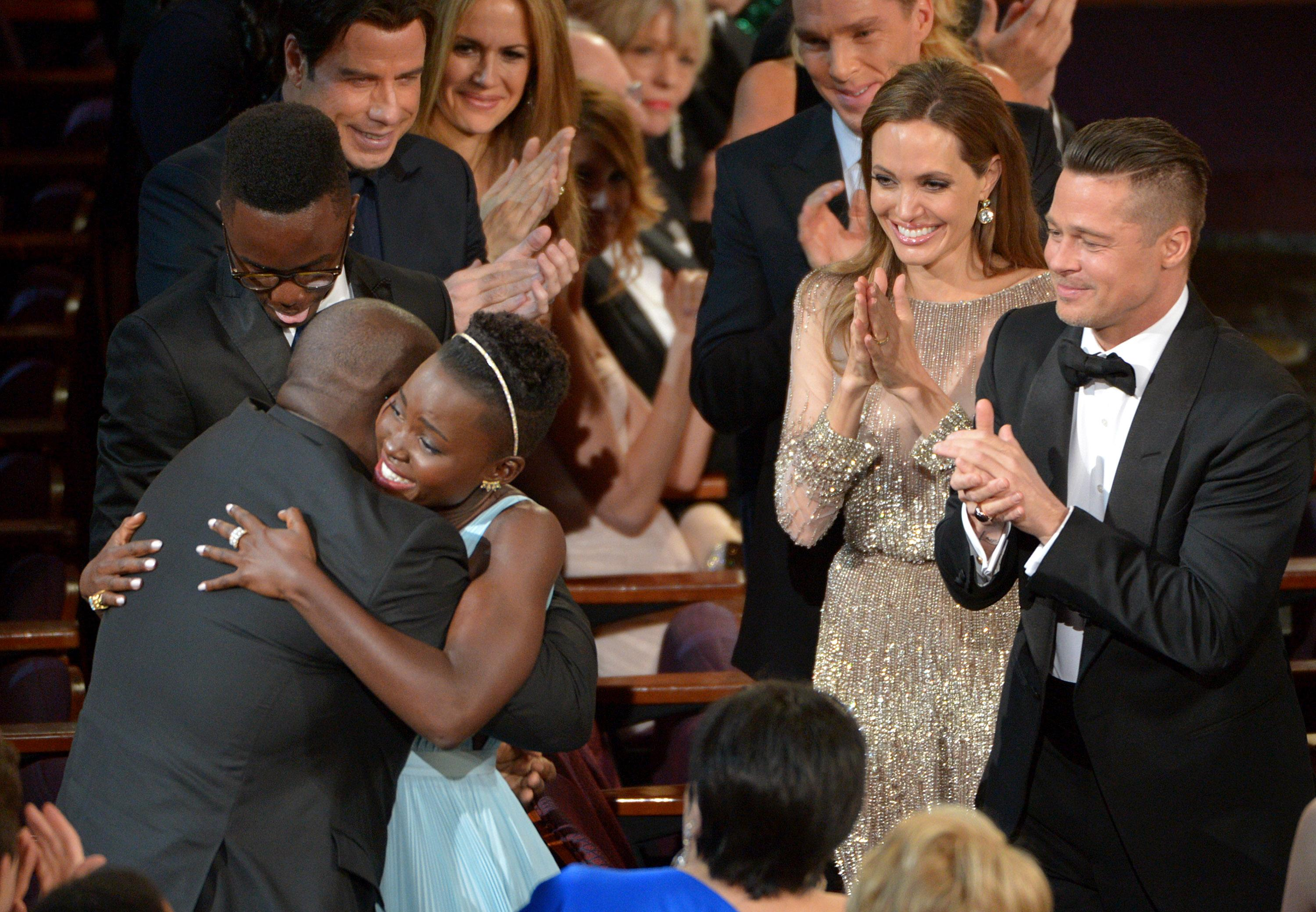 """Director Steve McQueen, left, congratulates Lupita Nyong'o on her win for best actress in a supporting role for """"12 Years a Slave"""" as her brother Peter, background from left, and actors John Travolta, Kelly Preston, Benedict Cumberbatch, Angelina Jolie and Brad Pitt, look on, during the Oscars at the Dolby Theatre on Sunday, March 2, 2014, in Los Angeles. (Photo by John Shearer/Invision/AP)"""
