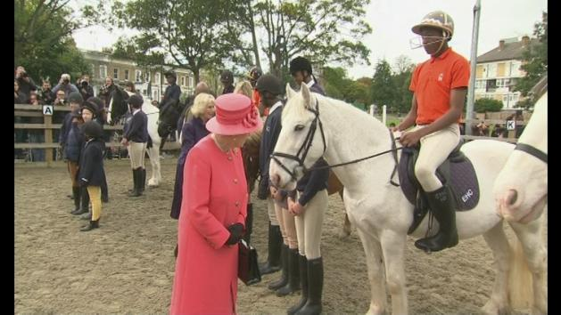 Queen talks to a horse, while Camilla feeds them sweets