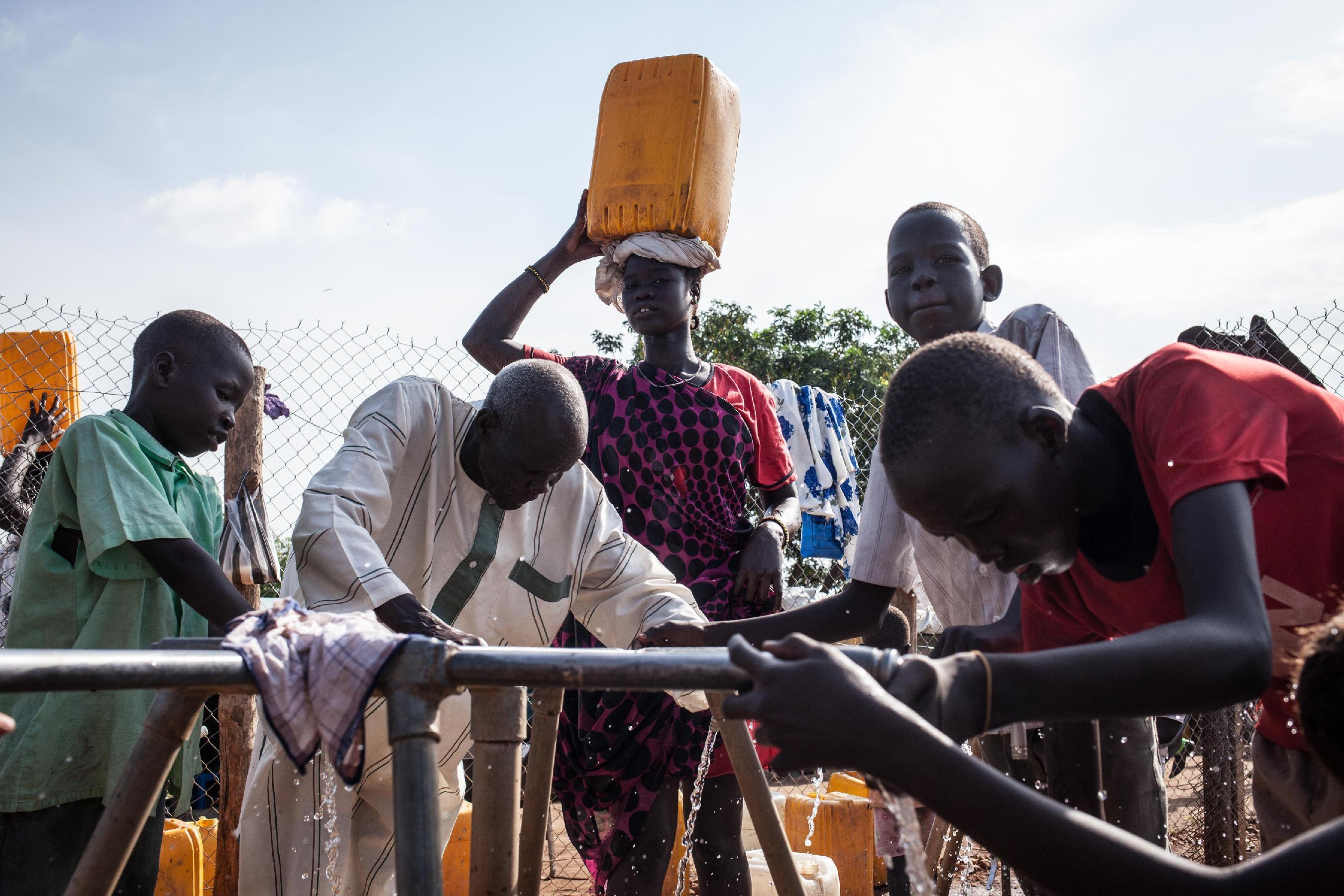 A woman carrying a bucket of water on her head looks on as refugees gather water at the Tomping Internally Displaced Persons (IDP) camp in Juba on July 2, 2014 (AFP Photo/Nichole Sobecki)