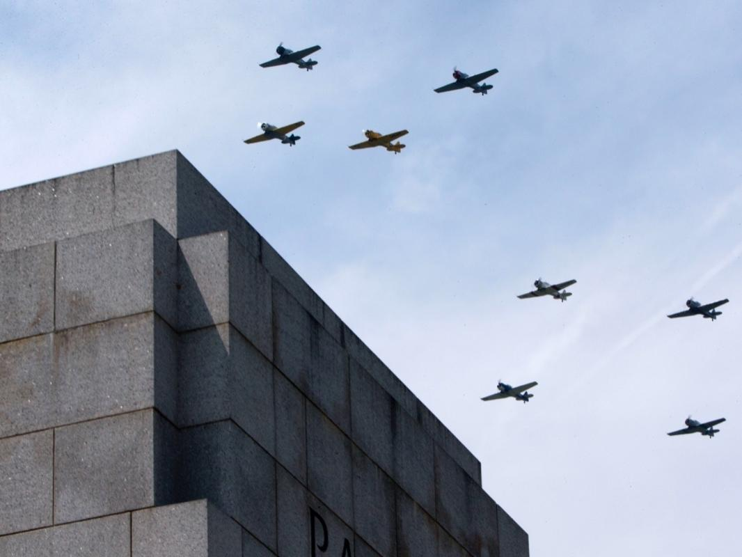 """World War II aircraft fly over the World War II Memorial in Washington, Friday, May 8, 2015, in honor of the 70th anniversary of Victory in Europe Day (VE Day), during the """"Arsenal of Democracy: World War II Victory Capitol Flyover."""""""