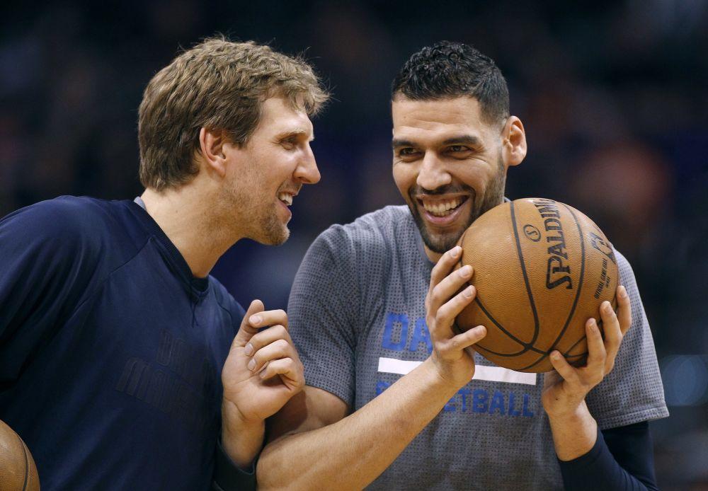 Dirk Nowitzki tells Salah Mejri a little secret: he's going to play until he's 65. (AP)