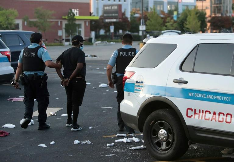 Police officers detain a man who was found inside of a Best Buy store after parts of the city had widespread looting and vandalism, on August 10, 2020 in Chicago, Illinois