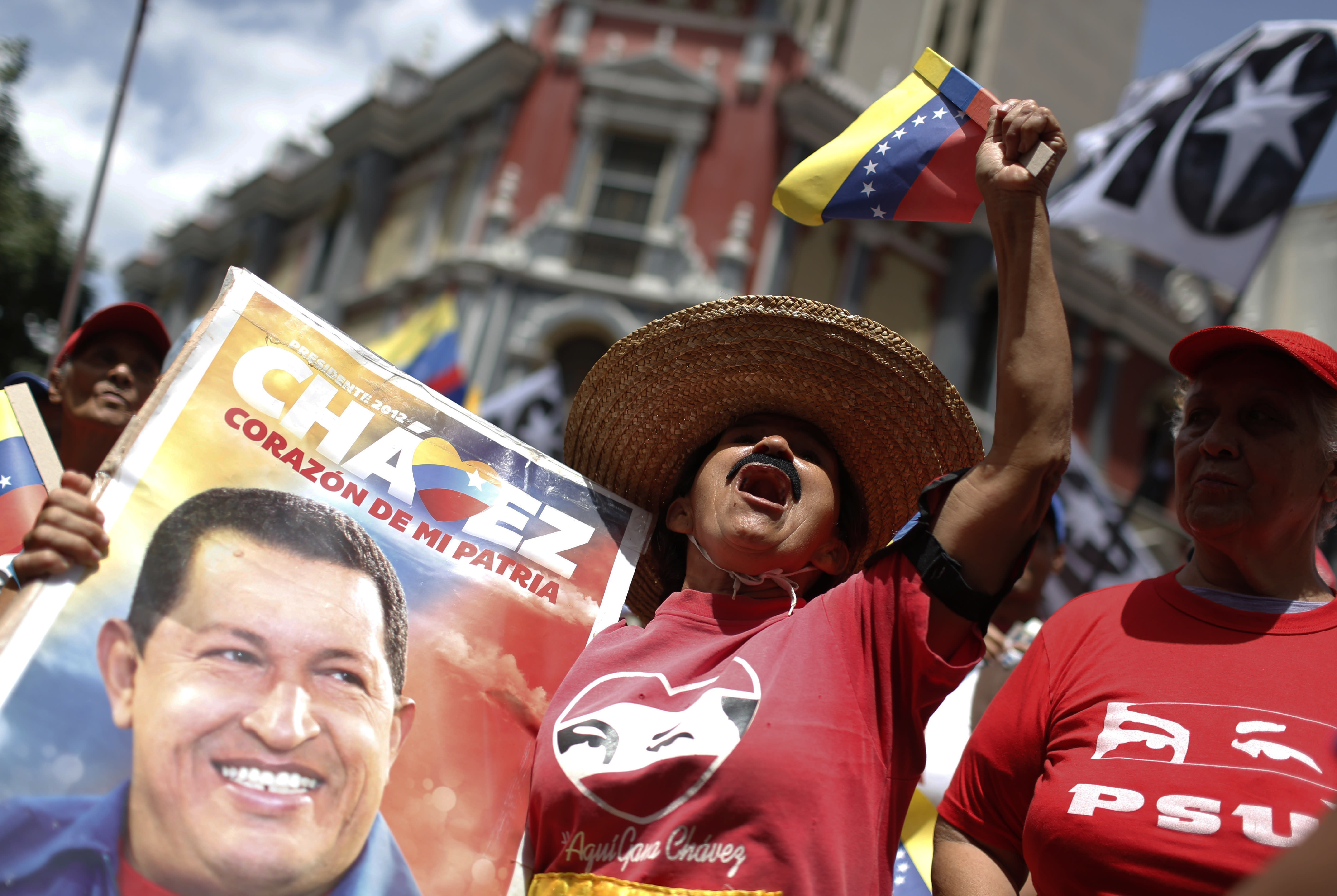 A government supporter holding an image of late Venezuelan President Hugo Chavez cheers during a rally on the sidelines of the Sao Paulo Forum in Caracas, Venezuela, Saturday, July 27, 2019. The Sao Paulo forum, held almost annually and hosted by Cuba last year, was founded as Latin American leftists sought to re-organize after the fall of the Berlin Wall in 1989. (AP Photo/Leonardo Fernandez)