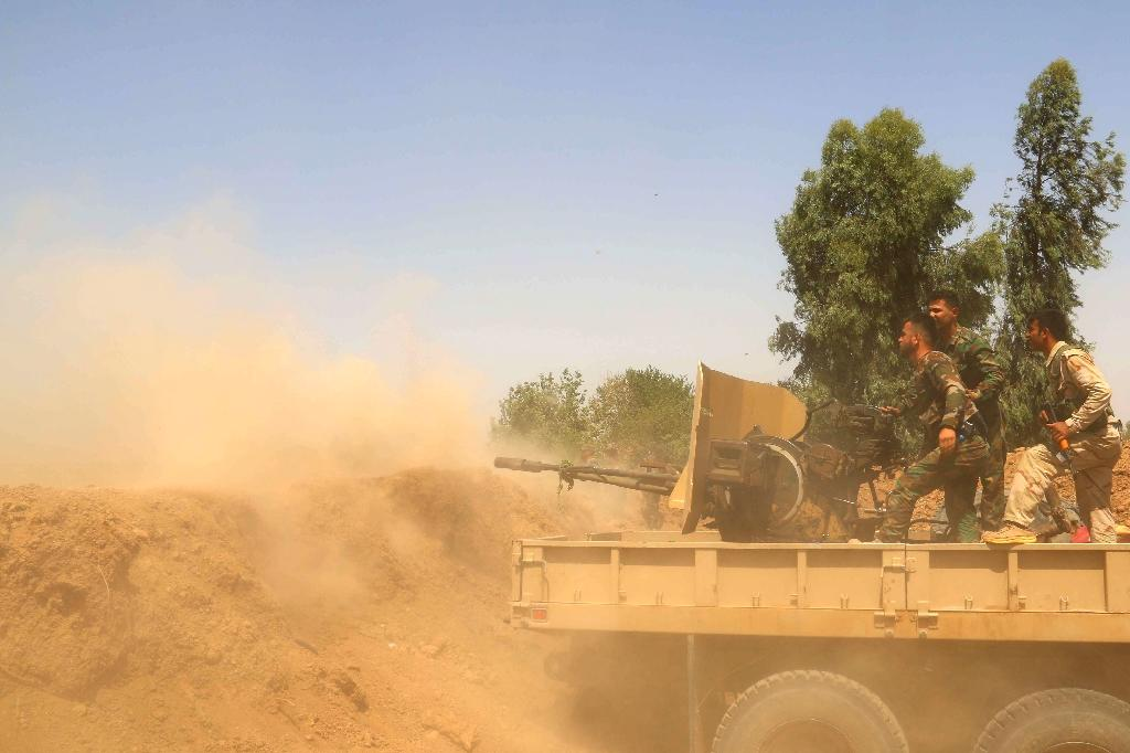 Iraqi Kurdish Peshmerga forces and Popular Mobilisation units fire towards Islamic State (IS) group positions on July 6, 2015, near the northern Iraqi oil capital of Kirkuk (AFP Photo/Marwan Ibrahim)