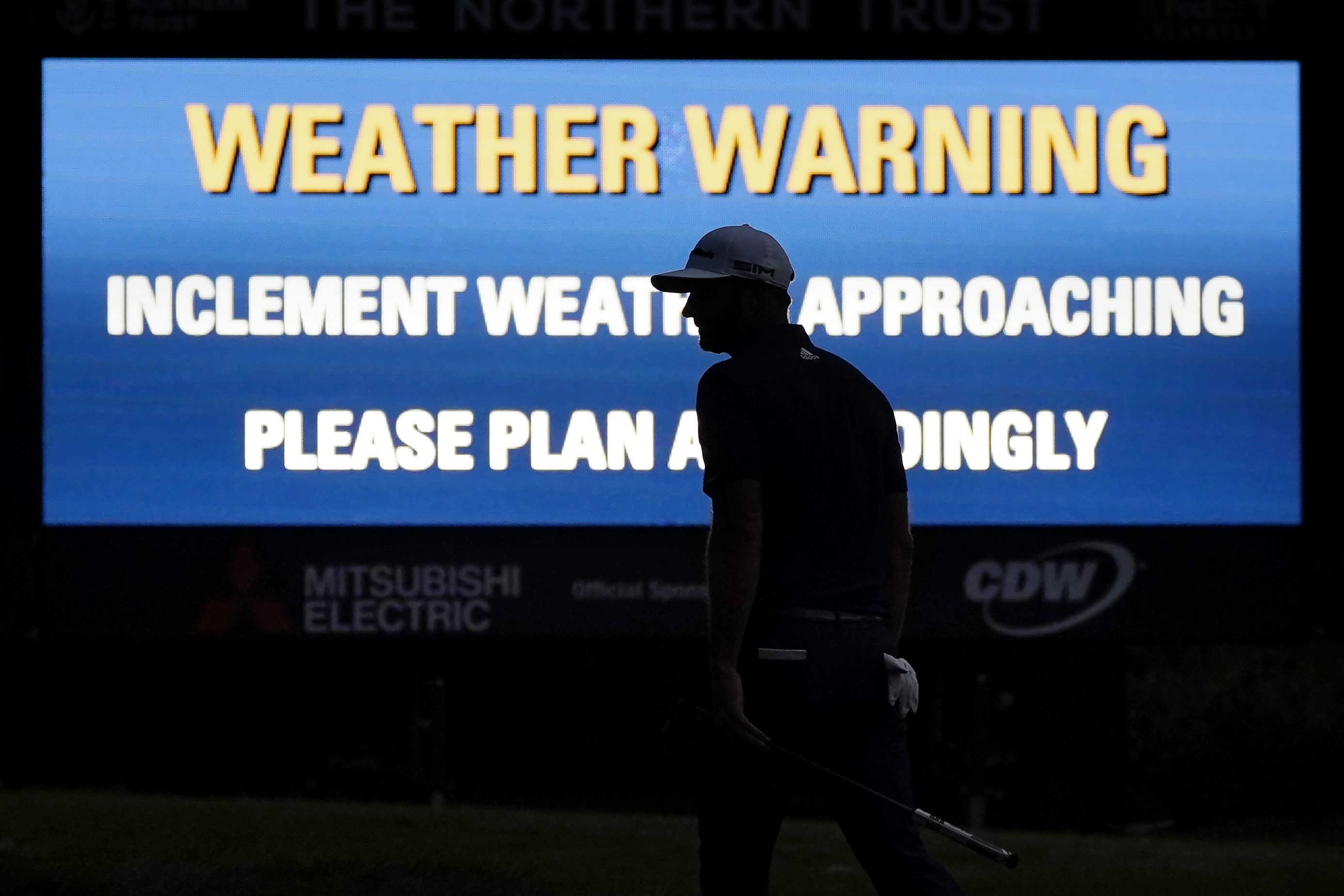 Dustin Johnson is silhouetted in the glow of a weather warning sign on the 17th hole during the final round of the Northern Trust golf tournament at TPC Boston, Sunday, Aug. 23, 2020, in Norton, Mass. (AP Photo/Charles Krupa)