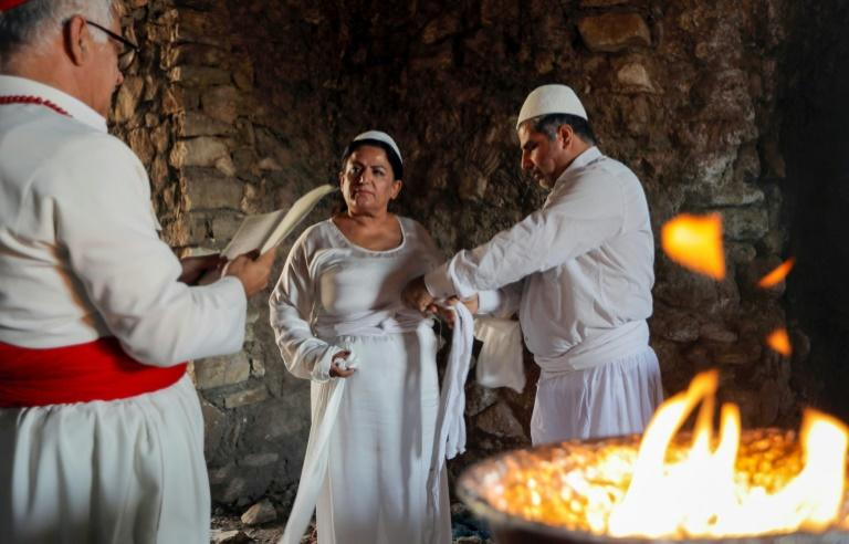 Iraqi Kurd Faiza Fouad takes part in a ritual ceremony in an ancient and ruined temple as she joins the millennia-old Zoroastrian religion (AFP Photo/SAFIN HAMED)