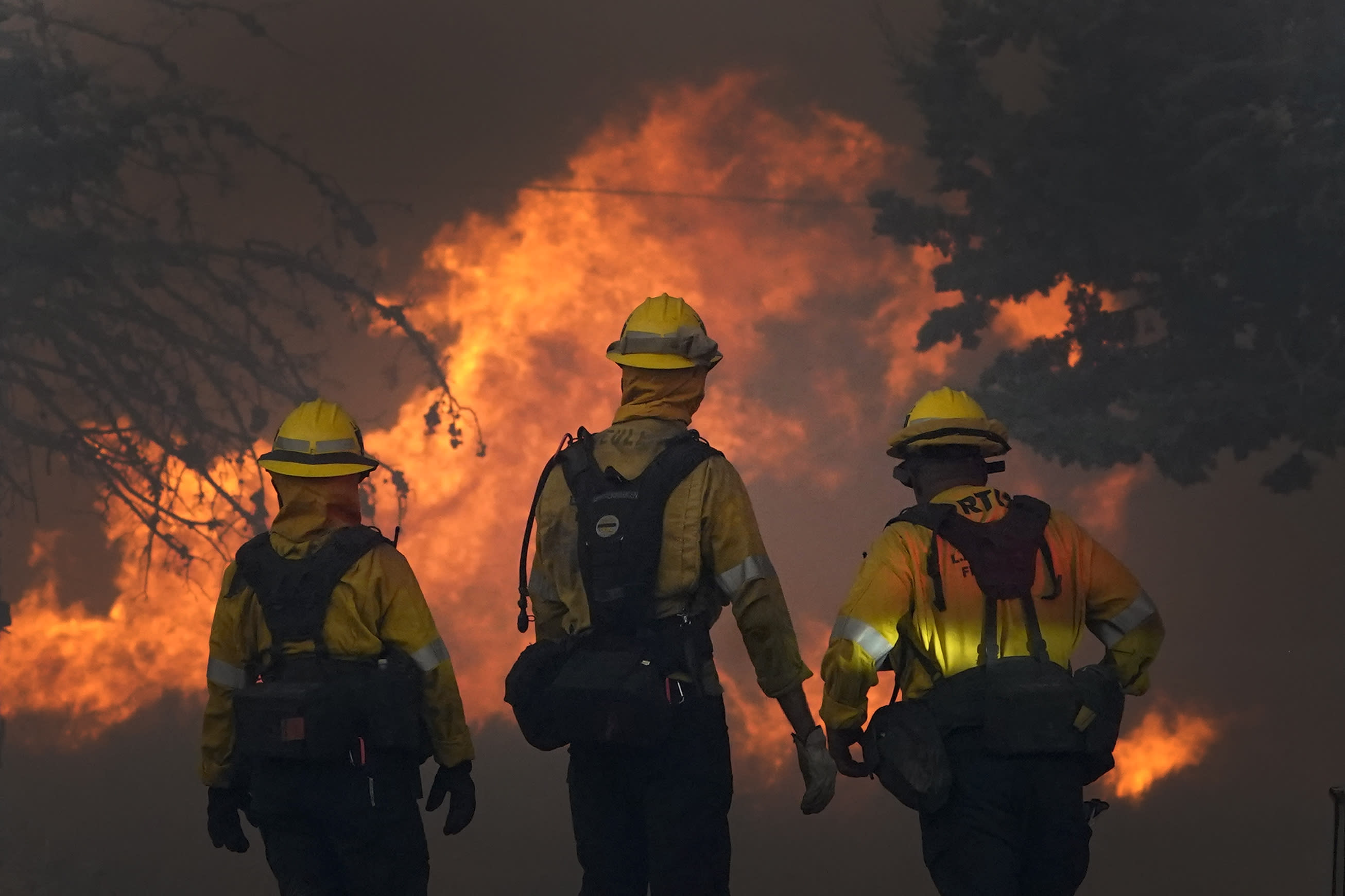 Members of a Los Angeles County Fire crew make a stand to protect a home from the advancing Bobcat Fire along Cima Mesa Rd. Friday, Sept. 18, 2020, in Juniper Hills, Calif. (AP Photo/Marcio Jose Sanchez)