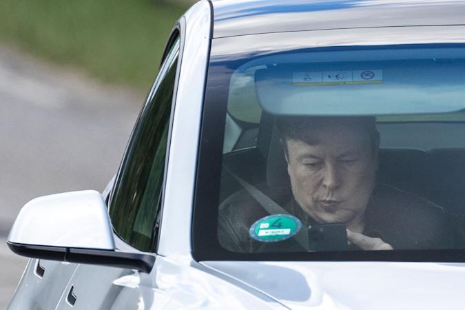"""Tesla CEO Elon Musk uses his mobile device as he sits in the car arriving to the construction site for the new plant, the so-called """"Giga Factory"""", of US electric carmaker Tesla in Gruenheide near Berlin, northeastern Germany. - The site still has only provisional construction permits, but Tesla has been authorised by local officials to begin work at its own risk. Tesla is aiming to produce 500,000 electric vehicles a year at the plant, which will also be home to """"the largest battery factory in the world"""", according to group boss Elon Musk. (Photo by Odd ANDERSEN / AFP) (Photo by ODD ANDERSEN/AFP via Getty Images)"""