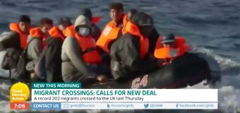 Migrant boat spotted in background during news