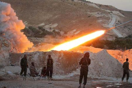 Free Syrian Army fighters launch a Grad rocket from Halfaya town in Hama province, towards forces loyal to Syria's President Bashar al-Assad stationed in Zein al-Abidin mountain