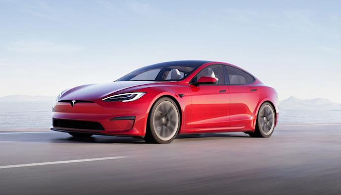 A Tesla Model S Plaid in red races down a coastal highway.