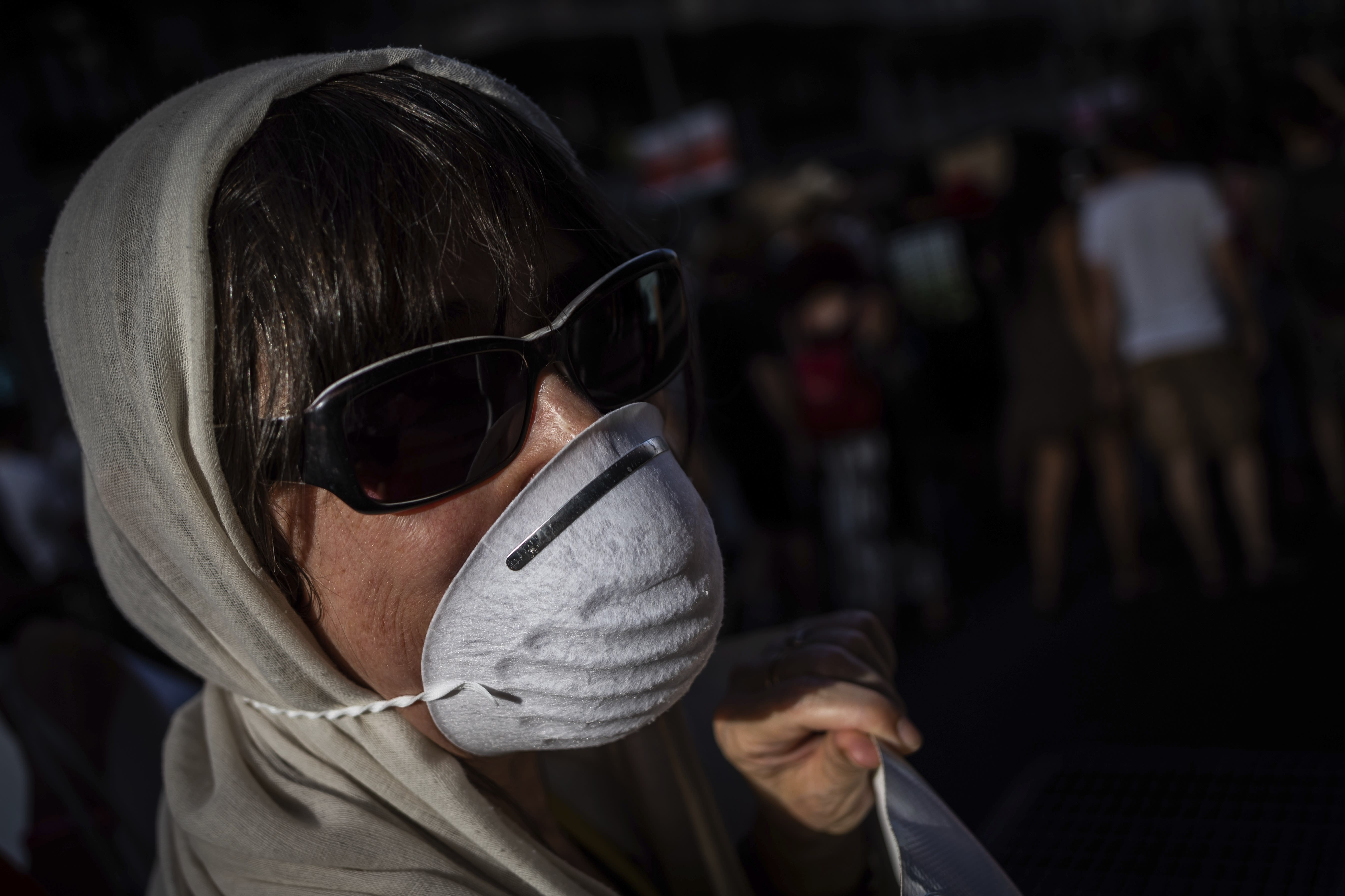 A citizen wears a mask during a rally in favor of a low-emission zone policy and against the new city council in Madrid, Spain, Saturday, June 29, 2019. The new municipality has decided to overturn ¨Madrid Central¨, an environment policy that banned most diesel and petrol cars within Madrid's downtown. The banner reads in Spanish ¨Less cars, better air¨. (AP Photo/Bernat Armangue)