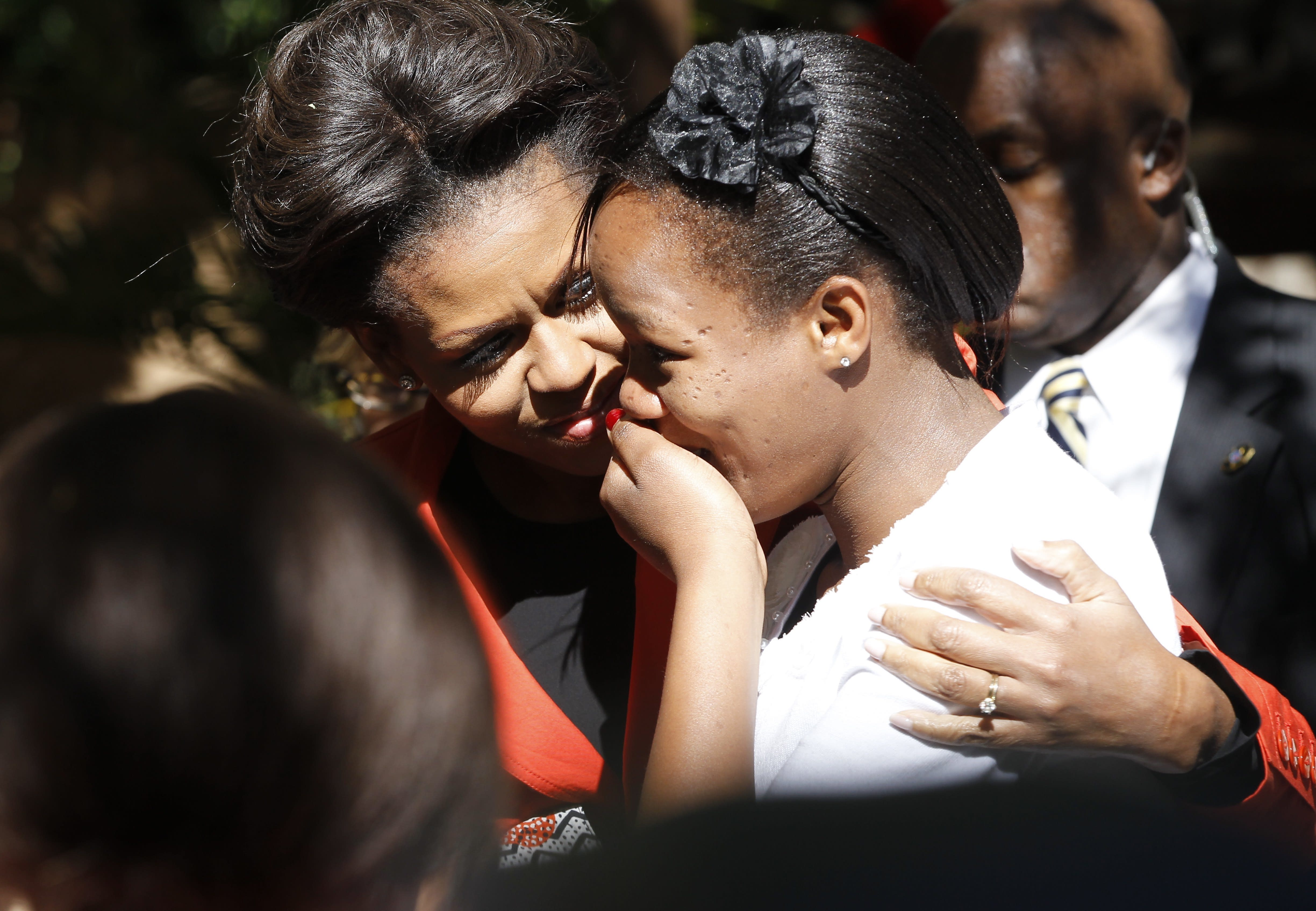 FILE - In this June 24, 2011, file photo, U.S. first lady Michelle Obama comforts a woman overcome with emotion as she greeted her at a multi-generational women leaders luncheon at the Sanitas Tea Garden in Gaborone, Botswana. When Melania Trump flies to Africa on her first extended international journey without the president, she'll be following in the footsteps of her recent predecessors. (AP Photo/Charles Dharapak, File)