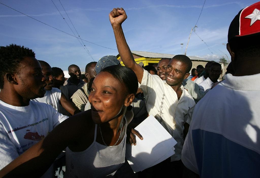 Former rebel commander Guy Philippe (C) raises a clenched fist amid supporters during a campaign stop in the Raboteau neighborhood of Gonaives, Haiti (AFP Photo/Roberto Schmidt)