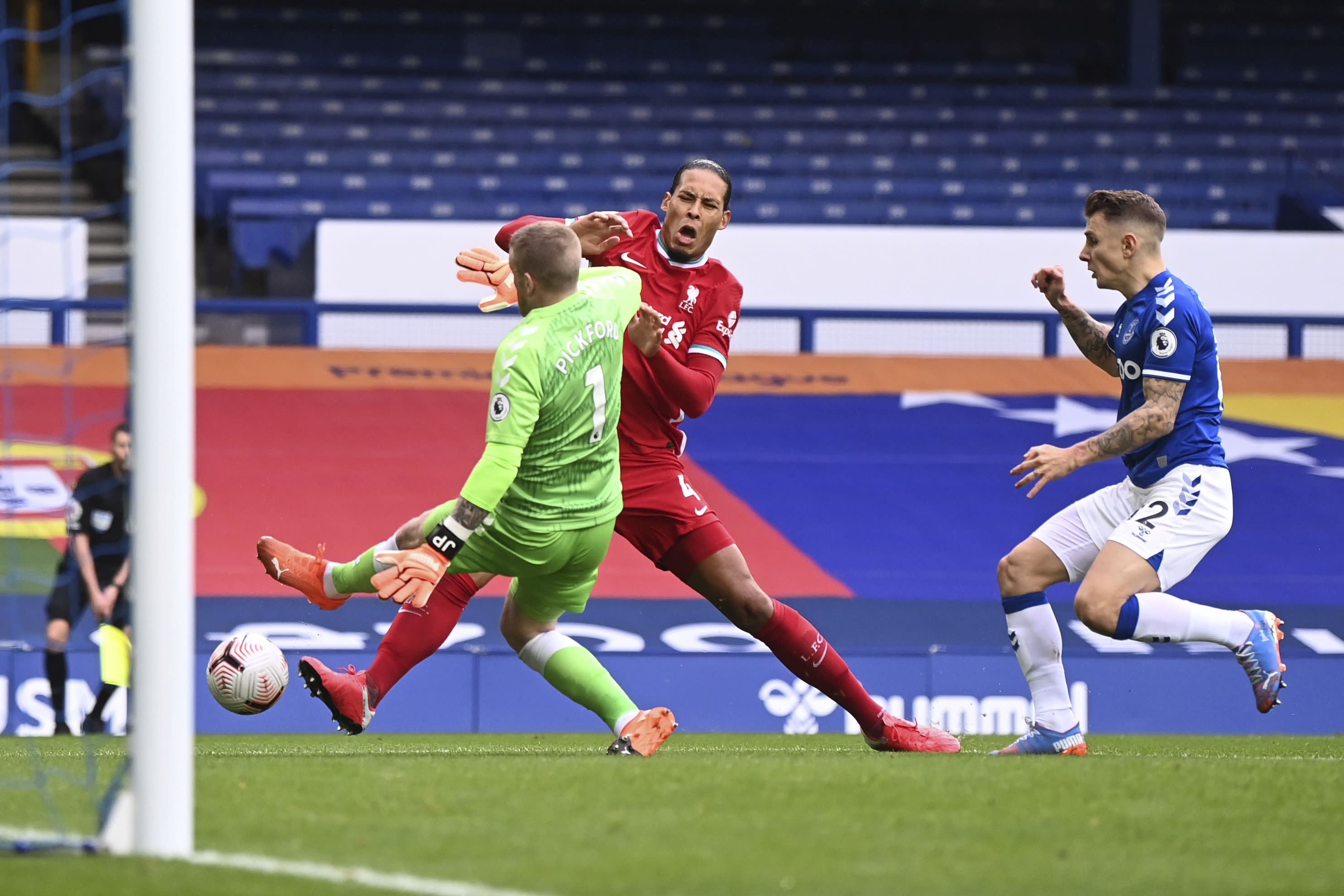 Liverpool's Virgil van Dijk, centre, is tackled and injured by Everton's goalkeeper Jordan Pickford, left, causing him to leave the match injured during the English Premier League soccer match between Everton and Liverpool at Goodison Park stadium, in Liverpool, England, Saturday, Oct. 17, 2020. (Laurence Griffiths/Pool via AP)