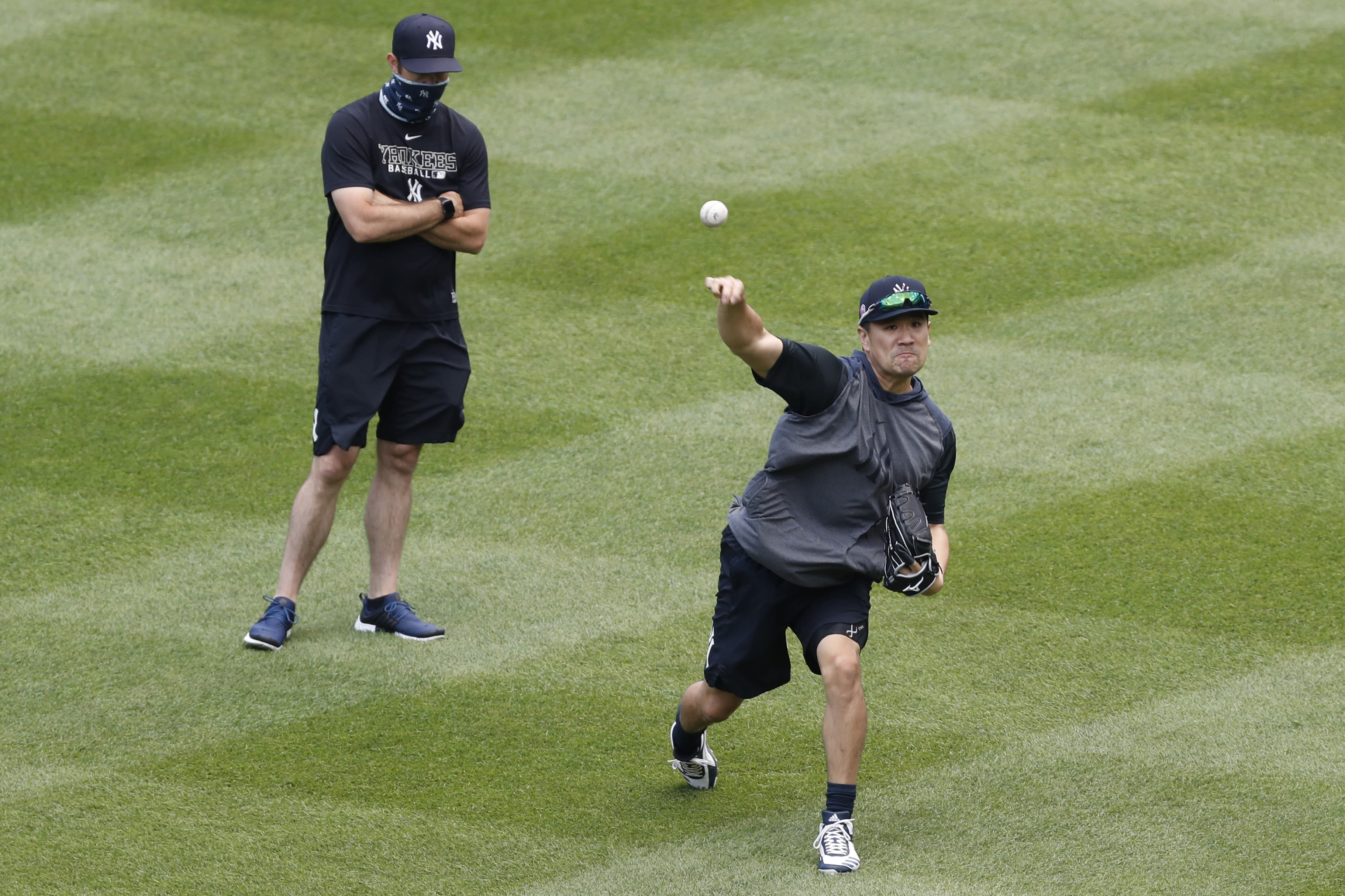 New York Yankees pitching coach Matt Blake, left, watches starting pitcher Masahiro Tanaka throw in the outfield at the Yankees summer baseball training camp, Wednesday, July 15, 2020, at Yankee Stadium in New York. Tanaka was struck in the head by a line drive off the bat of Giancarlo Stanton on July 4th. (AP Photo/Kathy Willens)