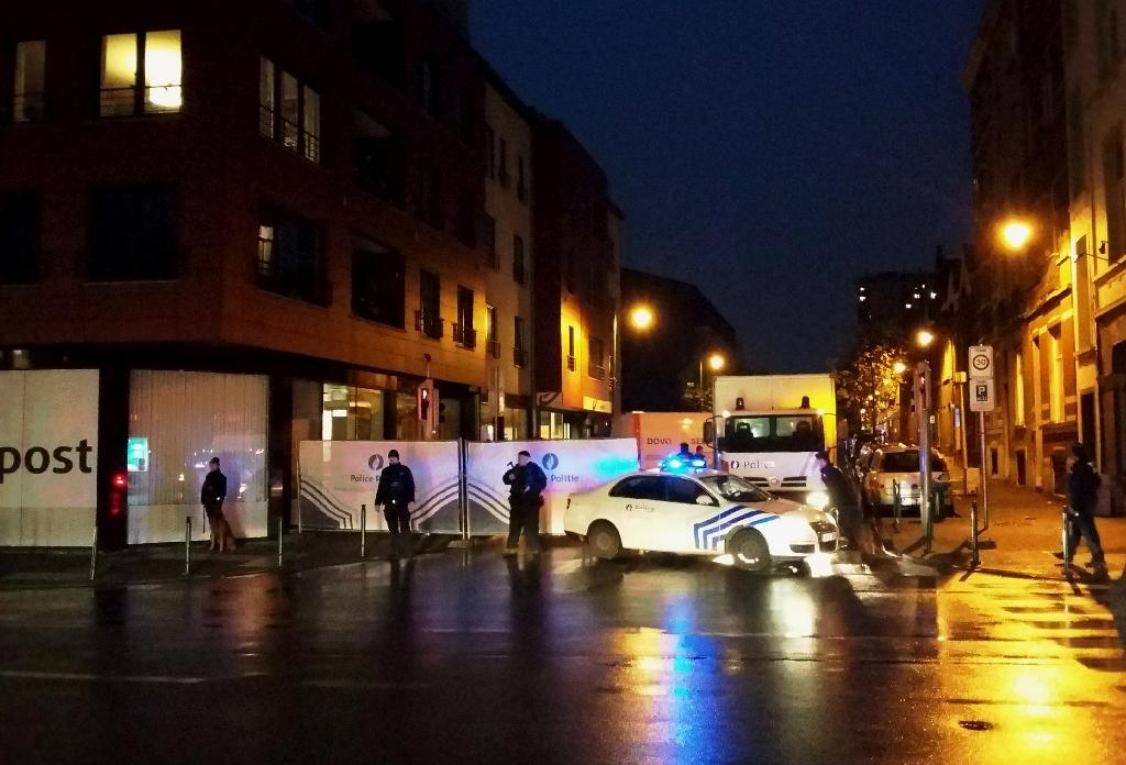 A photo taken on November 14, 2015 with a mobile phone shows Belgian police blocking a street during a police raid possibly in connection with the attacks in Paris, in Brussels' Molenbeek district (AFP Photo/Hendrik Devriendt)