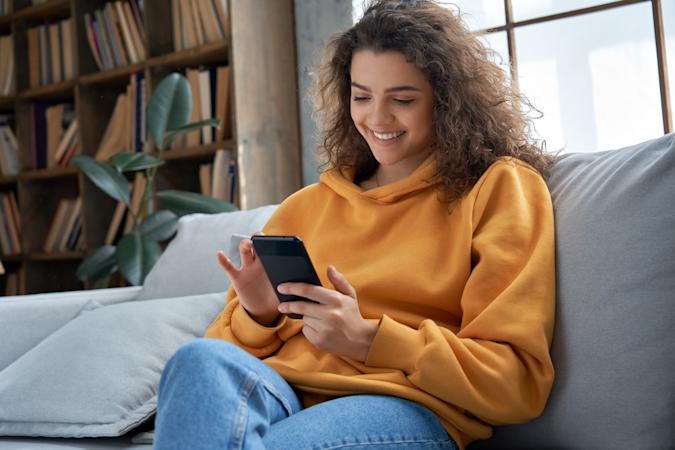 Happy millennial hispanic teen girl checking social media holding smartphone at home. Smiling young latin woman using mobile phone app playing game, shopping online, ordering delivery relax on sofa.