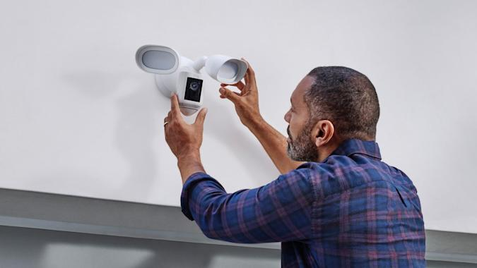 Image of a man installing a new Ring Floodlight Cam Wired Pro.