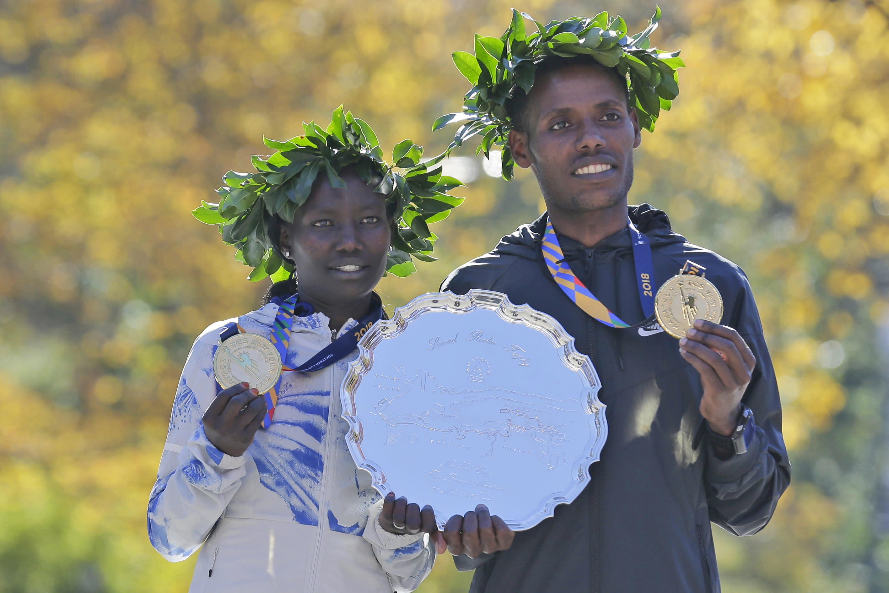<p>First-place finishers Mary Keitany of Kenya, left, and Lelisa Desisa of Ethiopia pose for a picture at the finish line of the New York City Marathon in New York, Nov. 4, 2018. (Photo: Seth Wenig/AP) </p>