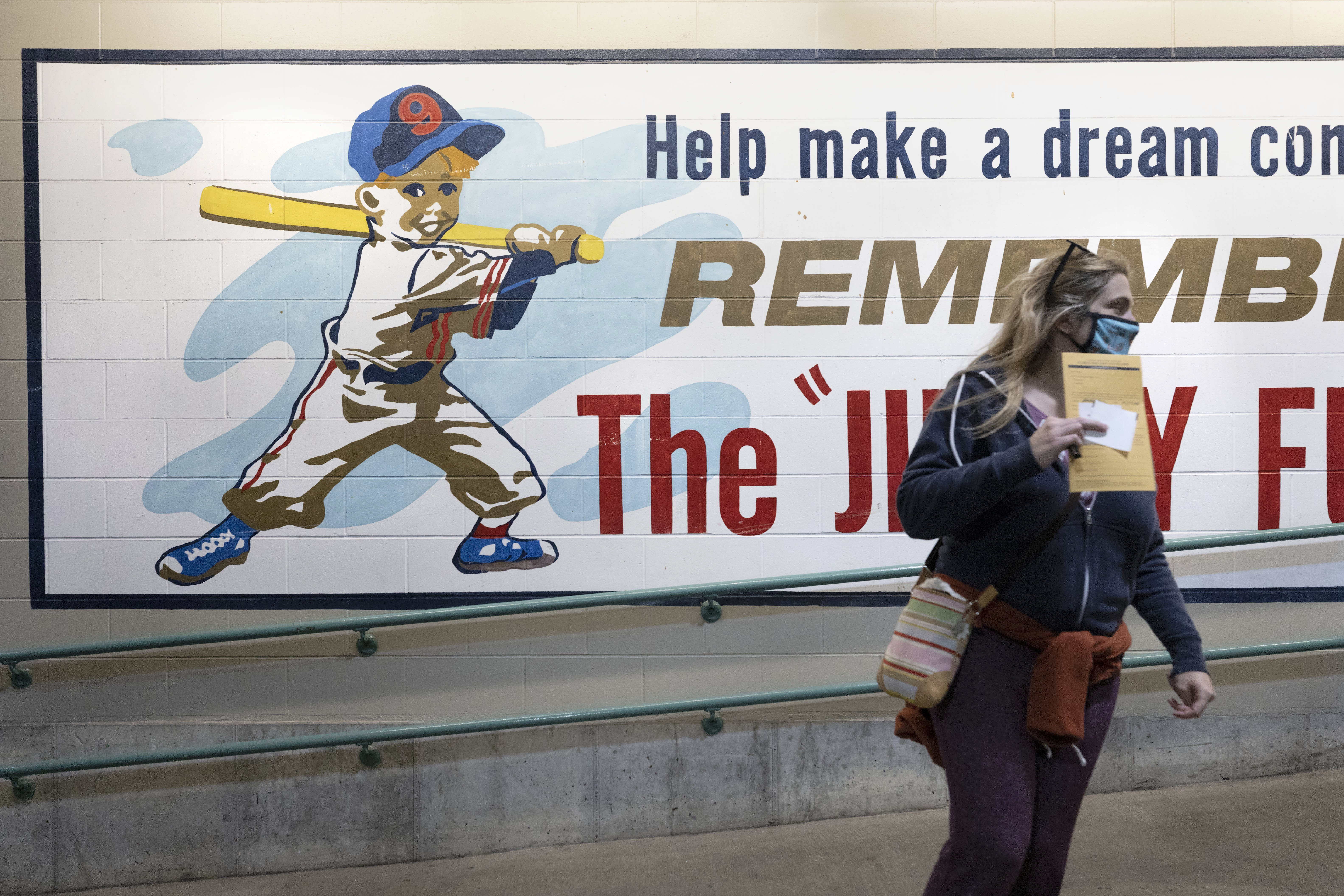 A woman holds her ballot as she heads to a voting booth in the concourse at Fenway Park, Saturday, Oct. 17, 2020, in Boston. (AP Photo/Michael Dwyer)