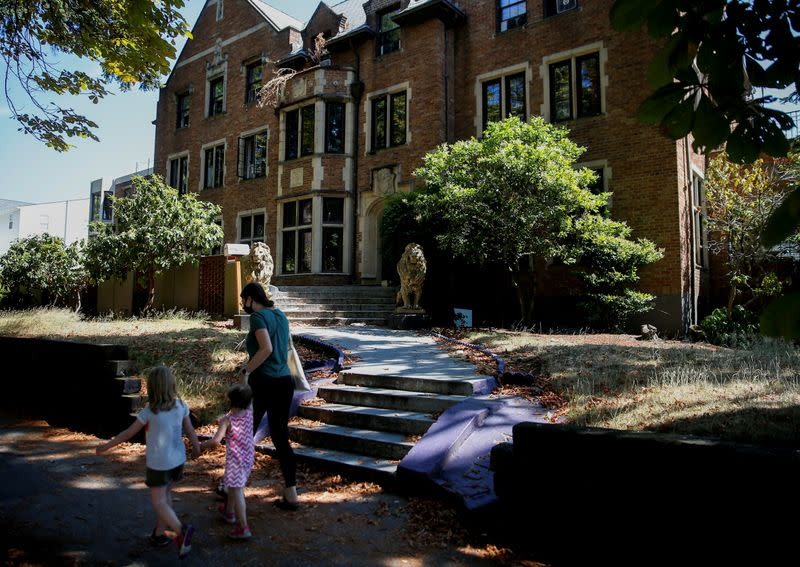 People walk by a fraternity house in the Greek Row area at the University of Washington in Seattle
