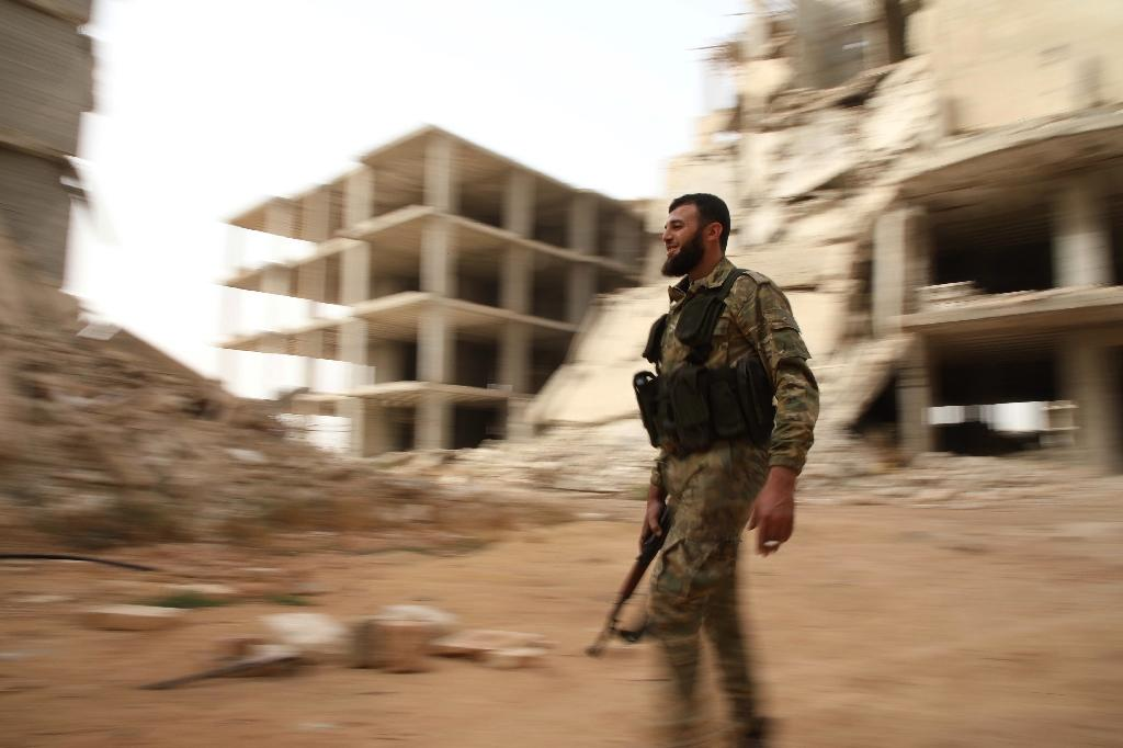 A Syrian rebel-fighter from the National Liberation Front walks in a street in the rebel-held Al-Rashidin district of western Aleppo's countryside near Idlib province, on October 15, 2018 (AFP Photo/Aaref WATAD)