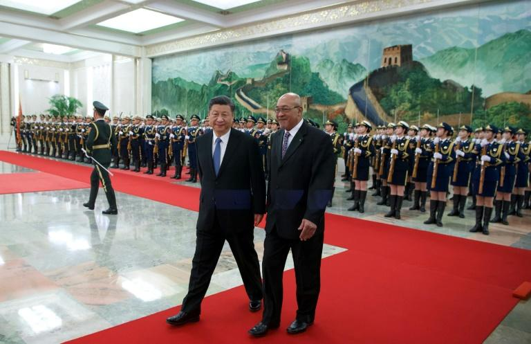 Suriname's then president Desi Bouterse walks with China's President Xi Jinping past a military honor guard at the Great Hall of the People in November 2019 as Beijing seeks stronger economic ties
