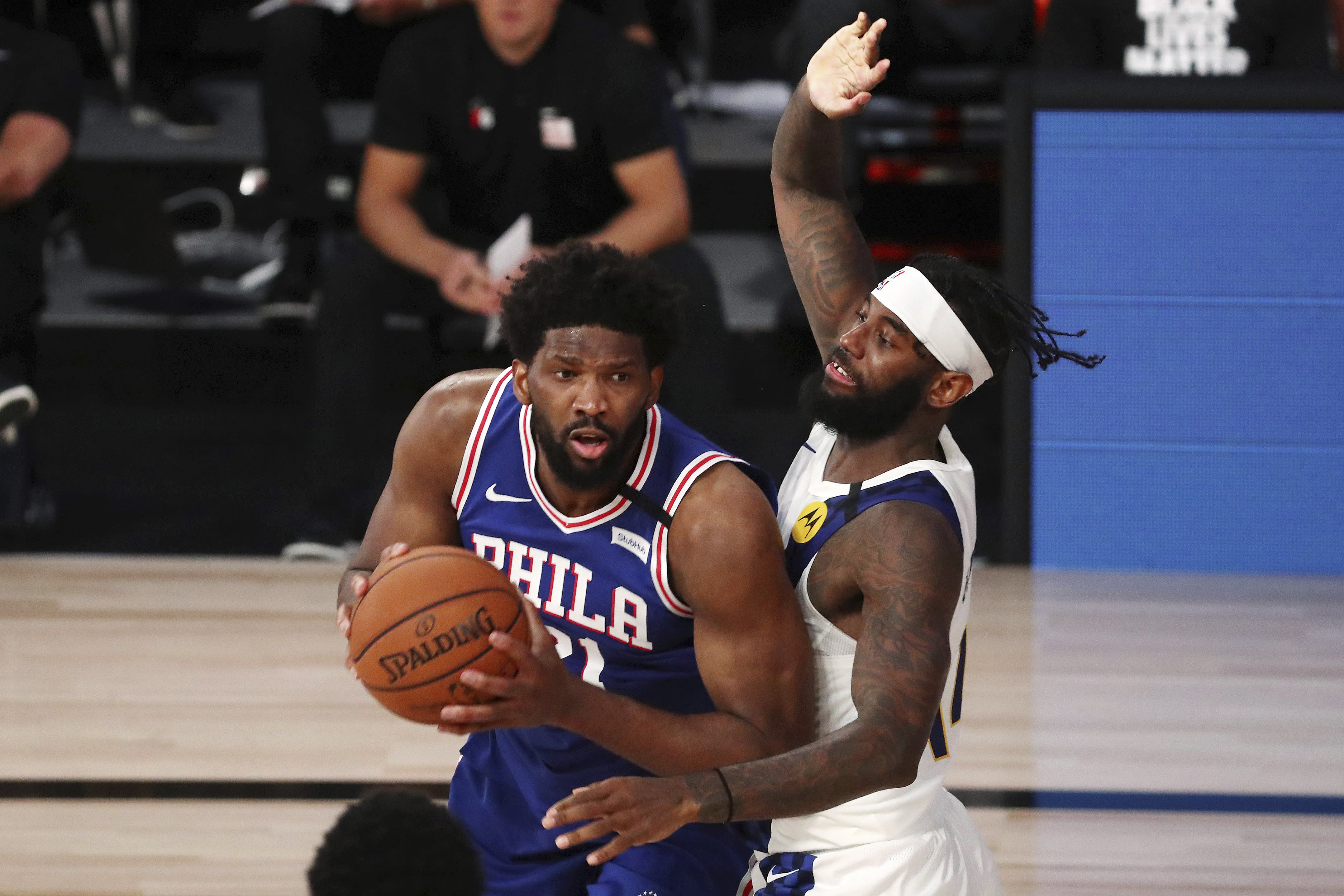 Philadelphia 76ers center Joel Embiid (21) drives to the basket against Indiana Pacers forward JaKarr Sampson during the third quarter of an NBA basketball game Saturday, Aug. 1, 2020, in Lake Buena Vista, Fla. (Kim Klement/Pool Photo via AP)