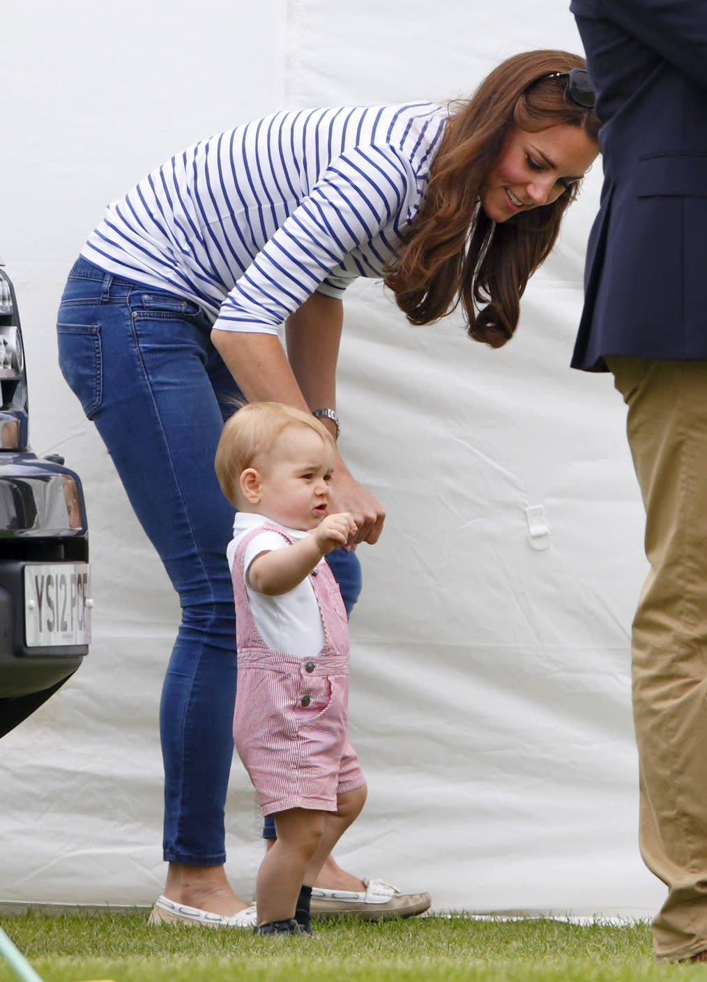 Prince George of Cambridge walks holding his Catherine, Duchess of Cambridge's hand as they watch Prince William, Duke of Cambridge & Prince Harry play in the Jerudong Trophy charity polo match. Kate is seen wearing a casual striped top and a pair of skinny jeans, while George is wearing an adorable pair of overalls.