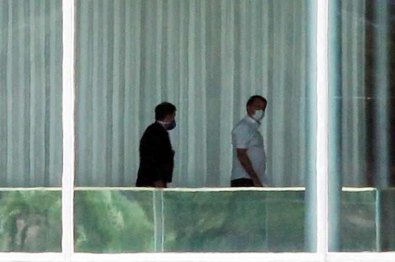 Brazilian President Jair Bolsonaro (R) walks with a consultant inside the Palacio Alvorada, in Brasilia, on March 13, 2020, after testing negative for the new coronavirus