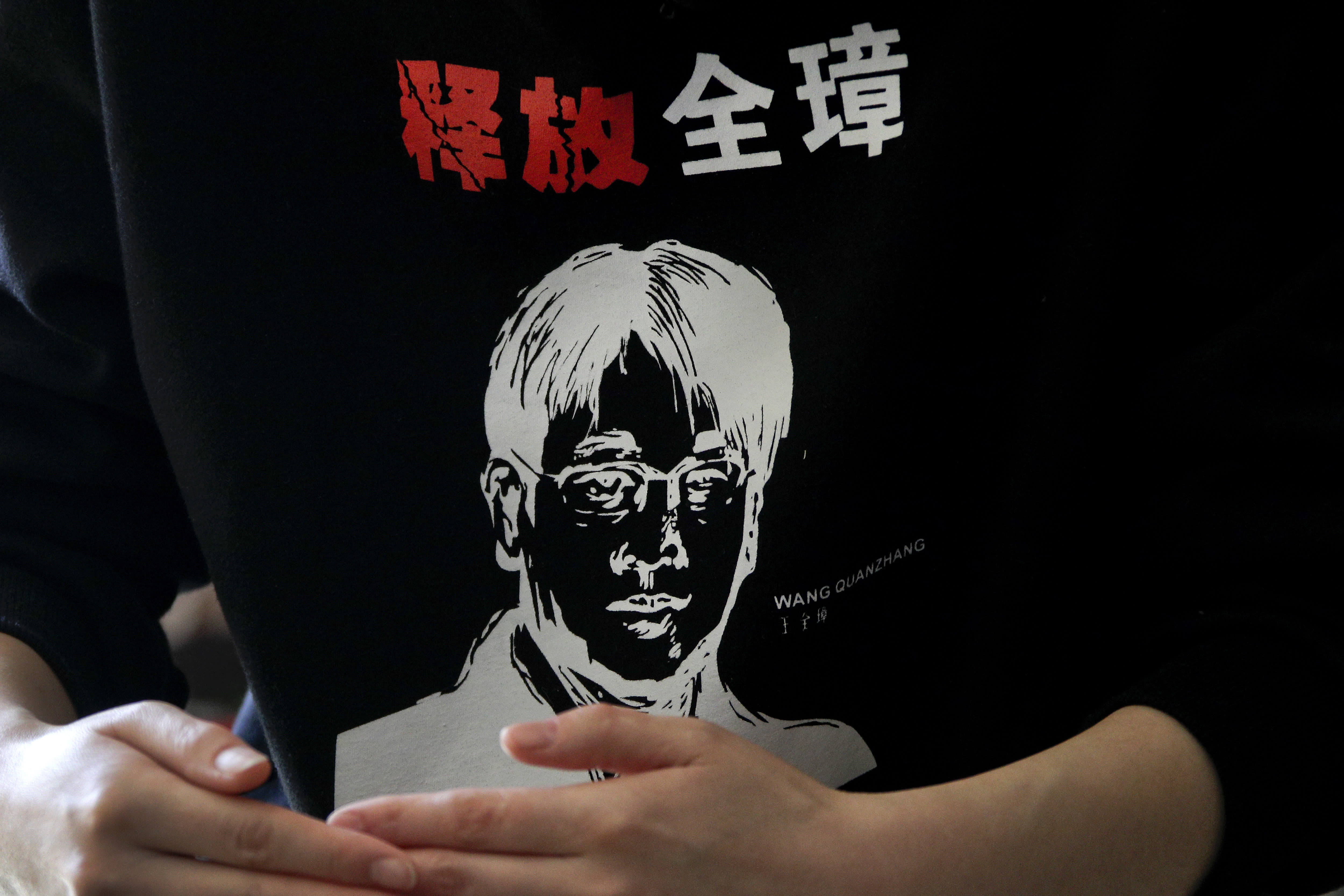 """Li Wenzu, wife of prominent Chinese human rights lawyer Wang Quanzhang wearing a sweater with her husband's portrait printed with the words """"Release Quanzhang"""" speaks at her house in Beijing, Monday, Jan. 28, 2019. Wang was sentenced to 4 and half years in prison on the charge of subversion of state power Monday, more than three years after he was detained in a wide-ranging crackdown on the legal profession. (AP Photo/Andy Wong)"""