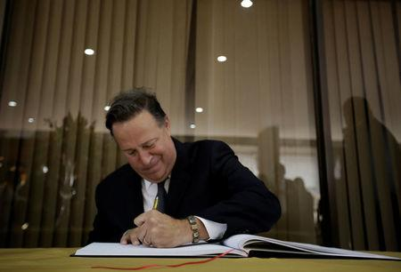 Panama's President Juan Carlos Varela signs a guest book during a welcoming ceremony at Presidential house in San Jose, Costa Rica
