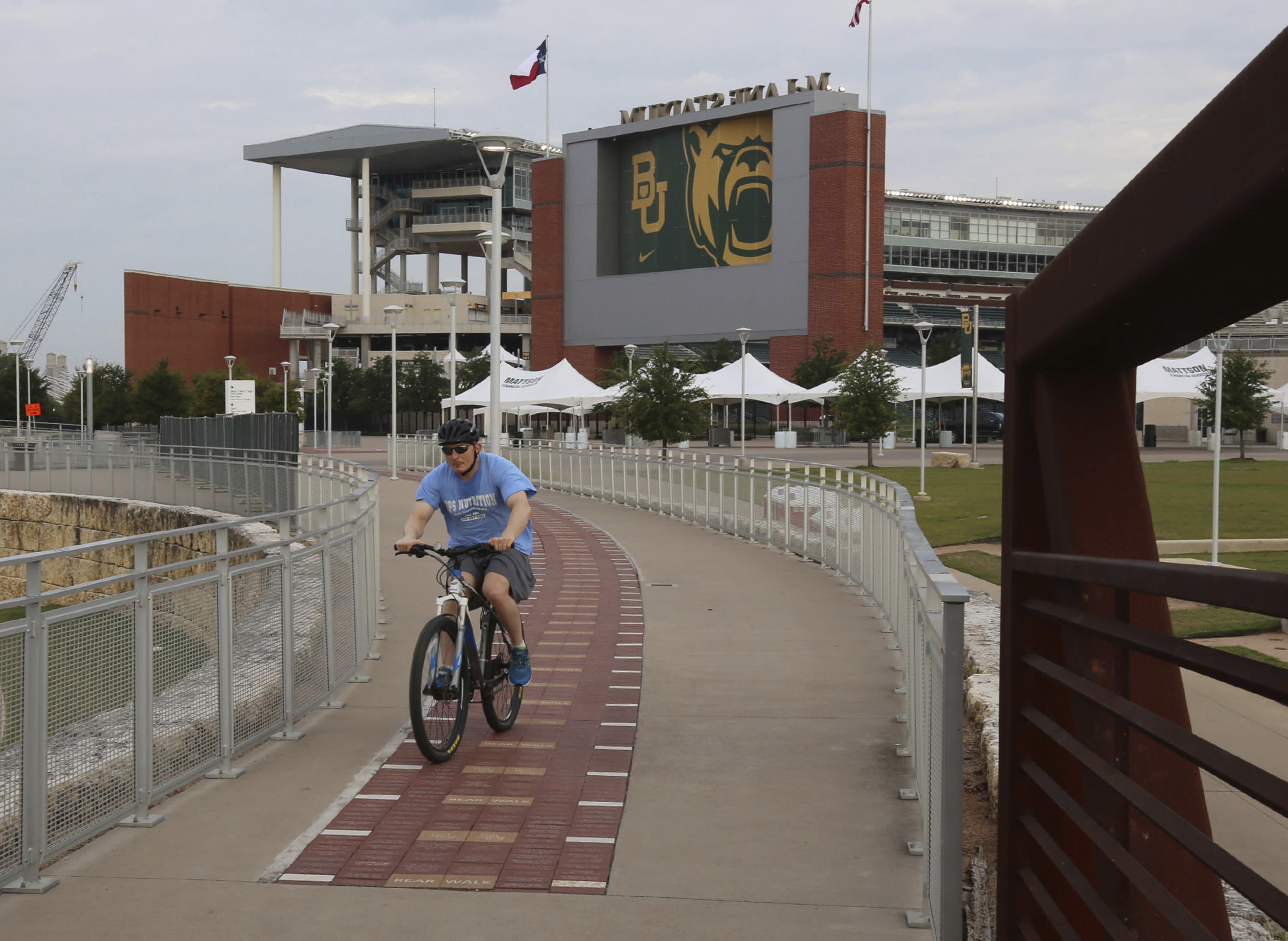 A bicyclist makes his way past Baylor University's McLane Stadium, Thursday, Sept. 17, 2020, in Waco, Texas. Baylor's season opener against Houston, scheduled less than a week ago, was one of two FBS NCAA college football games postponed Friday, Sept. 18, 2020, the day before before they were supposed play. (Rod Aydelotte/Waco Tribune-Herald via AP)