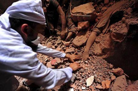 A rescue worker tries to find the remains of the garment workers, who died inside the rubble of the collapsed Rana Plaza building, in Savar