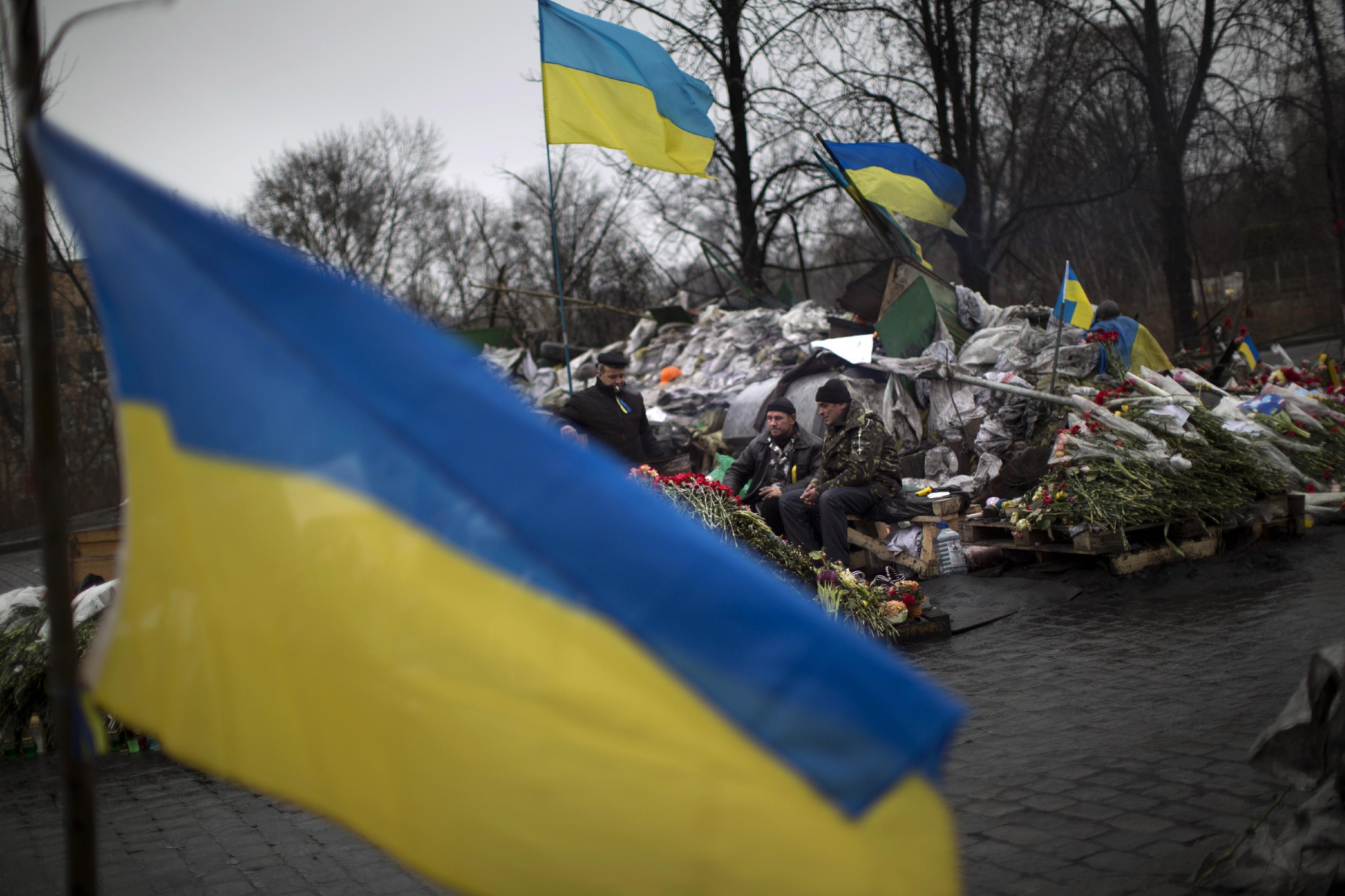 "Anti-Yanukovych protesters guard a barricade on a street heading to Kiev's Independence Square, in Ukraine, Wednesday, March 5, 2014. Stepping back from the brink of war, Vladimir Putin talked tough but cooled tensions in the Ukraine crisis Tuesday, saying Russia has no intention ""to fight the Ukrainian people"" but reserves the right to use force. As the Russian president held court in his personal residence, U.S. Secretary of State John Kerry met with Kiev's fledgling government and urged Putin to stand down. (AP Photo/Emilio Morenatti)"