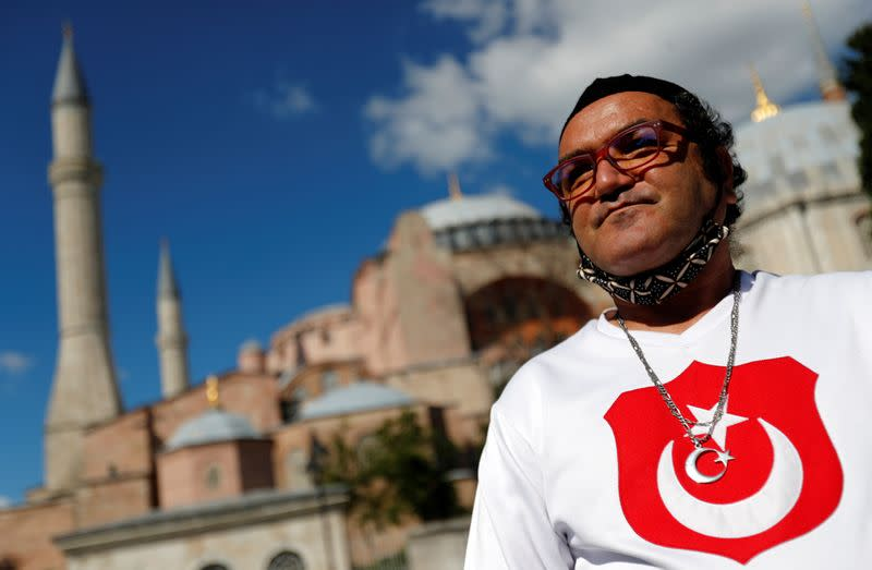 A man wears a shirt with the Turkish flag in front of the Hagia Sophia or Ayasofya, after a court decision that paves the way for it to be converted from a museum back into a mosque, in Istanbul