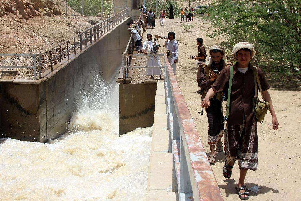 Armed Yemenis walk next to a dam in Marib province after heavy rain on April 22, 2016 (AFP Photo/Nabil Hassan)
