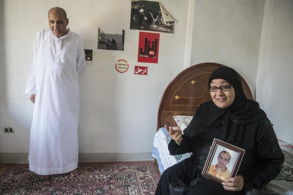 Reda Mahrous, holds a photo of her son, jailed Egyptian photographer Mahmoud Abdel Shakour Abou-Zeid, as her husband Abedel Shakour Abu Zeid looks on, at their home in Cairo (AFP Photo/Khaled Desouki)