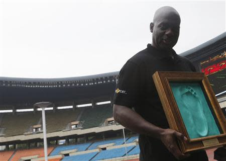 Sprinter Ben Johnson of Canada holds a cast of his footprint made after running on the track at the Seoul Olympic Stadium in Seoul