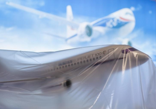 A Russian Sukhoi Superjet SSJ-100 model aircraft sits under plastic sheeting at the 2014 Farnborough Airshow in Farnborough, southern England