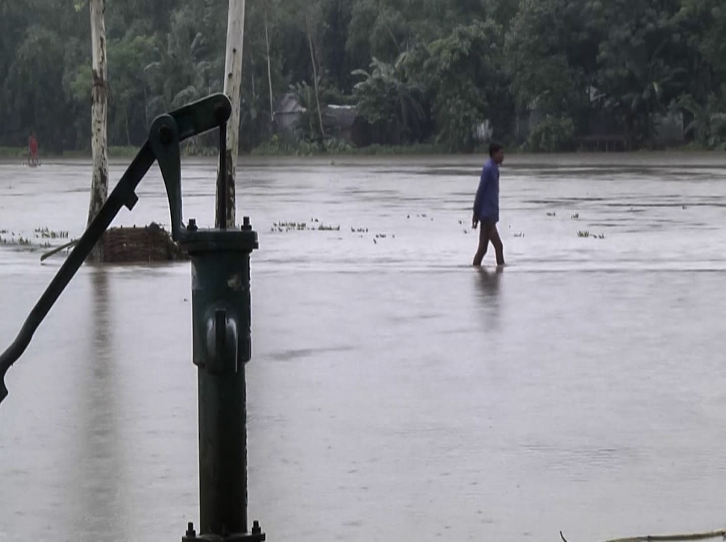 In this video grab taken from the Associated Press Television footage a Bangladeshi man walks through flood waters in Lalmonirhat, Bangladesh, Monday, July 13, 2020. Heavy flooding is worsening in parts of Bangladesh, with over 1 million villagers marooned or leaving their homes for higher ground along with their cattle and other belongings, officials and volunteers said Tuesday. (AP Photo/Bayezid Ahmed)