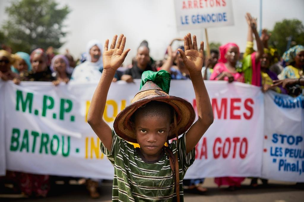 """A Fulani boy marches in front of a sign that reads """"Stop the Genocide"""" during a silent June 2018 demo in response to a massacre of civilians in Koumaga, in central Mali"""