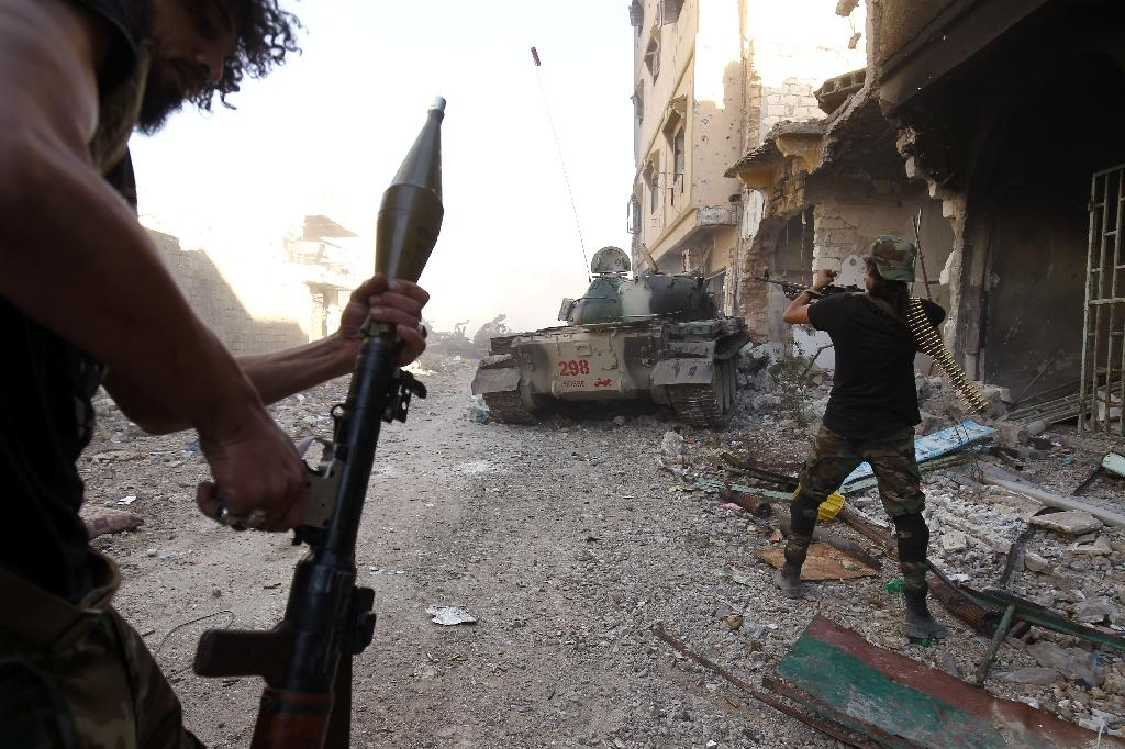 Members of the self-styled Libyan National Army, loyal to the country's eastern strongman Khalifa Haftar, open fire during clashes with militants in Benghazi on November 9, 2017