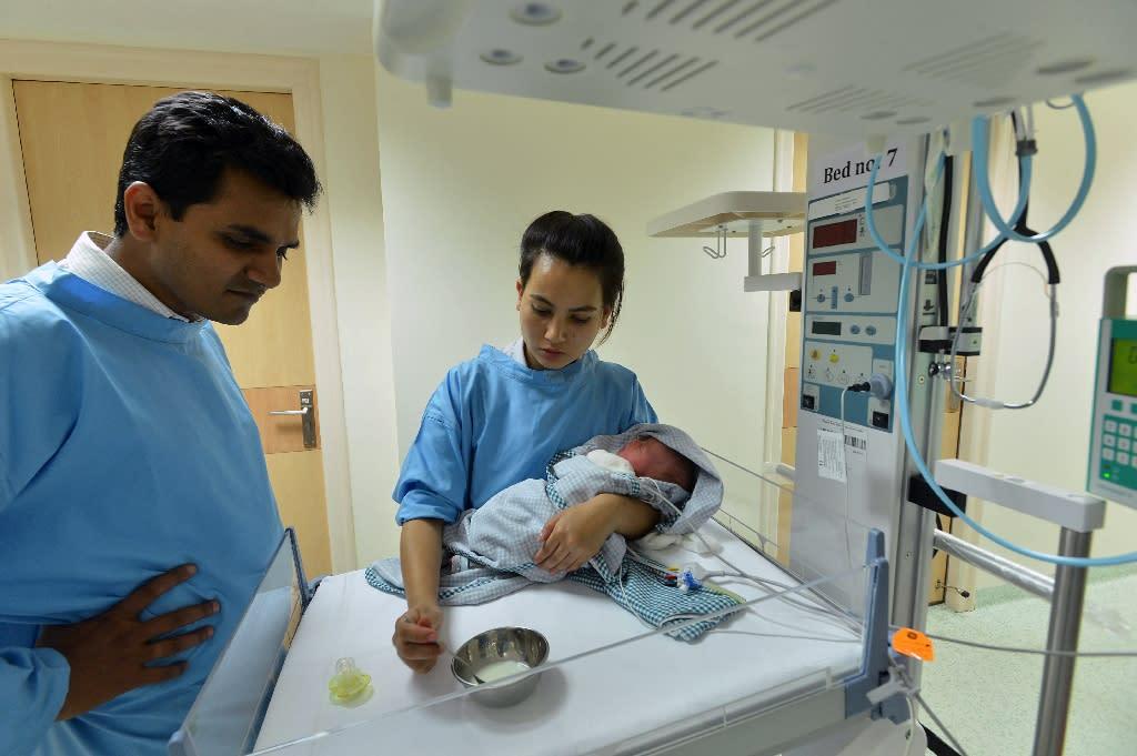 A nurse feeds a baby born to a surrogate mother in a hospital in Kathmandu on May 26, 2015 (AFP Photo/Ishara S.Kodikara)