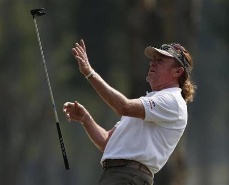 Defending champion Miguel Angel Jimenez from Spain throws his club after missing a putt on the ninth green during the second day of the European Tour Hong Kong Open golf tournament