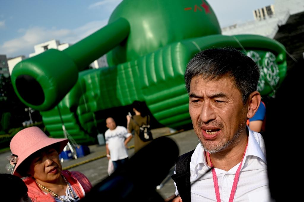 Li Xiaoming, a junior officer in China's military during the 1989 Tiananmen crackdown, stands in front of an inflatable tank artwork in Taipei