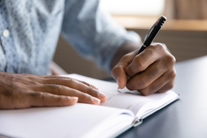 Close up view of african left-handed businessman writing in notebook, american male hands holding pen making notes planning new appointments information in organizer personal paper planner at desk