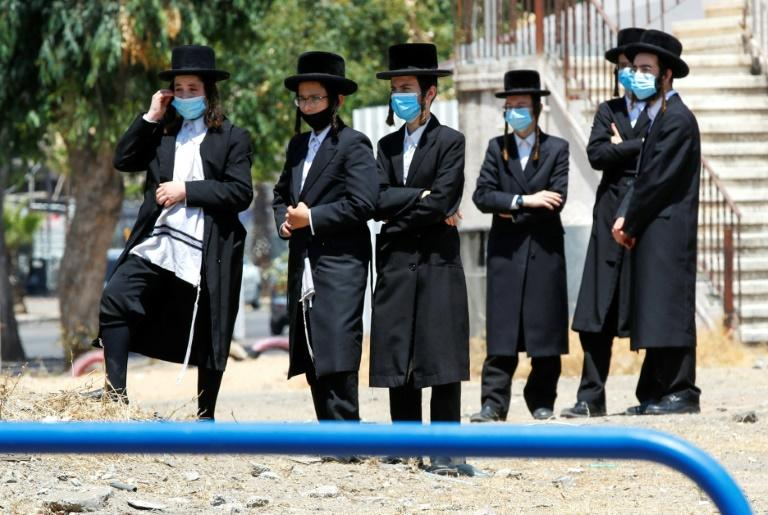 Ultra-Orthodox Jews in protective masks gather at the entrance of a neighbourhood that has been isolated following a recent increase in coronavirus cases in the southern coastal city of Ashdod, on July 2, 2020